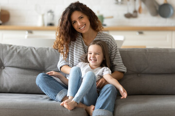 Close up portrait picture of smiling young mother with daughter sitting on couch at home. Happy...