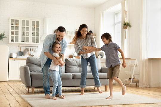Happy family playing funny game having fun together with little son and daughter in modern living room. Young dad and mother with adorable cute children doing exercises, enjoying weekend at home.