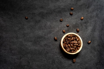 top view of a wooden bowl filled with roasted coffee bean on a dark slate background. horizontal format with copy space for text