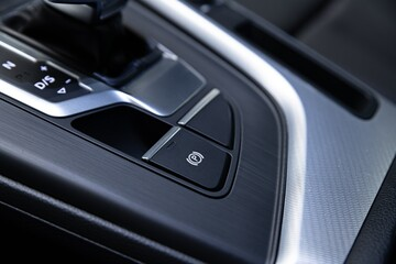 Parking brake. Electric handbrake switch. Modern car interior.