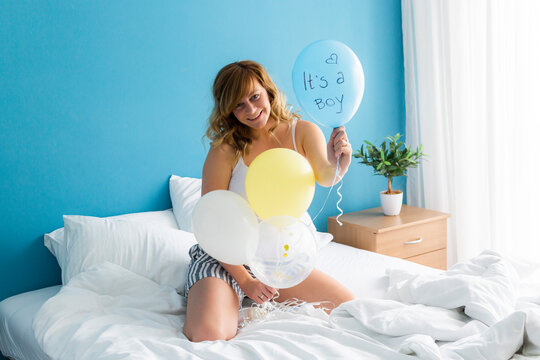 Happy pregnant woman celebrating in bed with balloons.
