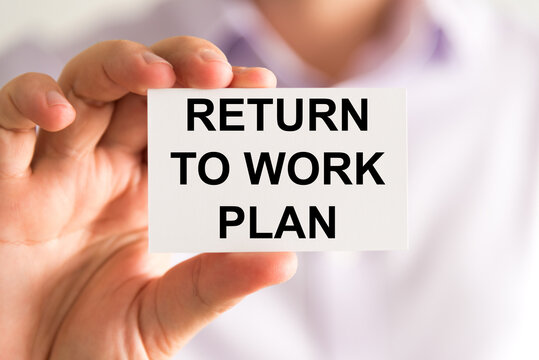 Businessman holding Returning To Work Plan message card