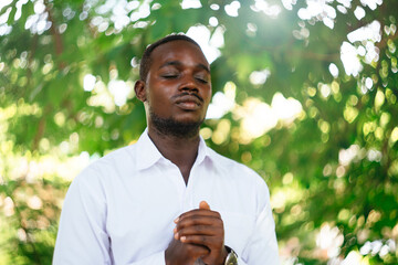 African man praying for god in the green nature.