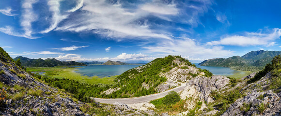 Montenegro Skadar Lake coast with mountains beautiful scenic view panorama. Blue sky water reflection sunny day outdoor Mediterranean summer wonderland background. European tourism vacation concept