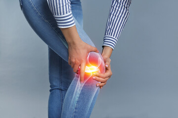 Woman suffering from knee pain on grey background, closeup