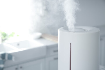 Modern air humidifier in kitchen, closeup. Space for text