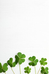 Photo sur Toile Inde Clover leaves on white wooden table, flat lay with space for text. St. Patrick's Day symbol