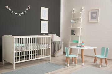 Cute baby room interior with modern crib near dark wall