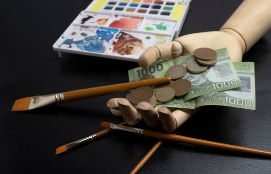 wooden hand with chilean money and brushes