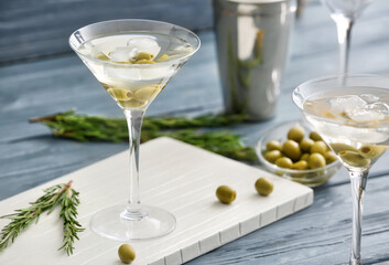 Glasses of tasty martini cocktail with olives on table