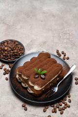 Classic tiramisu dessert on ceramic plate on concrete background