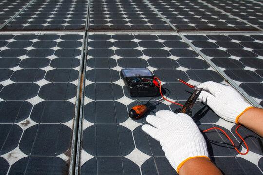 Technician repairing photovoltaic modules (Solar panels) in rural