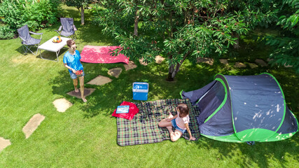 Aerial top view of campsite from above, mother and daughter having fun, tent and camping equipment under tree, family vacation in camp outdoors concept