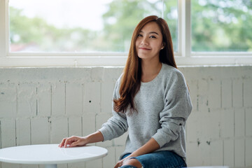 Portrait image of a beautiful young asian woman sitting in cafe with feeling happy