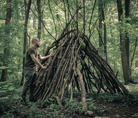 Fototapeta Man building a survival shelter in the forest. Shelter in the woods from tree branches. obraz