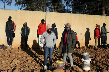 Job seekers stand behind somen selling fat cakes in Johannesburg