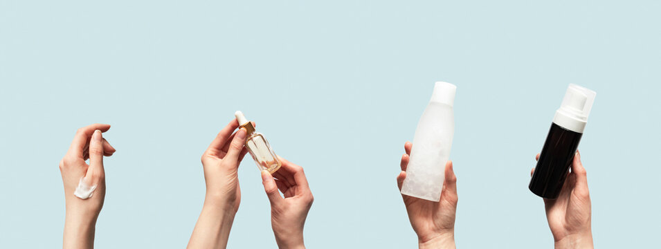 Hands up holding beauty cosmetic products isolated on blue background horizontal banner format. Woman takes oil serum, toner or tonic bottle, facial foam cleanser and smear smudge moisturizer cream
