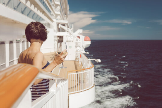 Beautiful lady in striped blue dress on deck of cruise ship with a glass of white wine