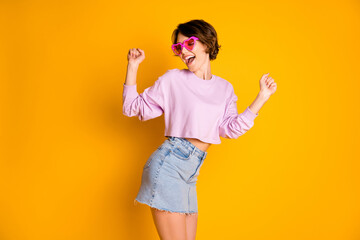 Portrait of enthusiastic funky youngster girl enjoy autumn rest relax raise fists have playful...