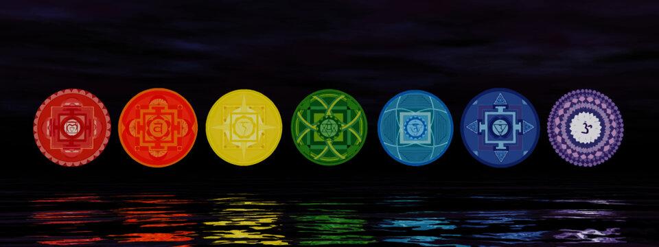Seven chakra symbols on the horizon line by night