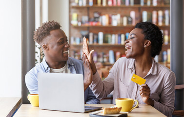 Online shopping. Millennial black couple with credit card making high five gesture near laptop at...