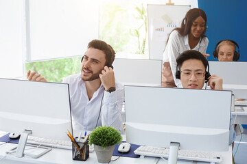 Group of helpline operators at work in modern call center office