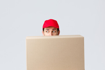 Packages and parcels delivery, covid-19 quarantine and transfer orders. Scared courier in red uniform cap, hiding behind customer order, looking left nervously, peeking at banner or advertisement