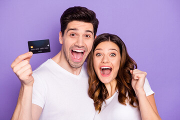 Portrait of ecstatic two married people hold credit card win bank cashback service help raise fists...
