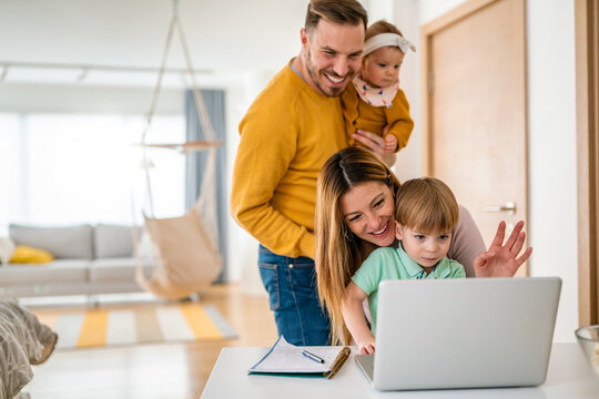 Happy family at home using computer, waving while in a live video chat