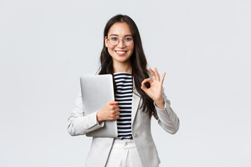 Business, finance and employment, female successful entrepreneurs concept. Young confident businesswoman in glasses, showing okay gesture, hold laptop, guarantee best service quality