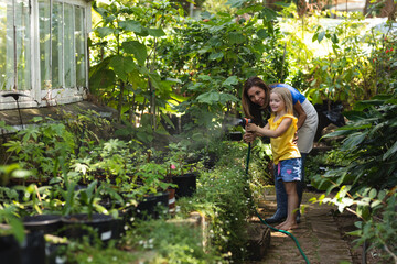 A Caucasian woman and her daughter looking at plants together in a sunny garden