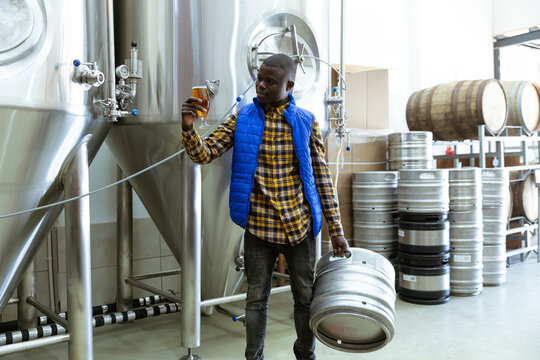African American man holding a pint of beer and holding a tank in a brewery