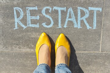 Restart concept, top view on woman legs and text written in chalk on gray sidewalk