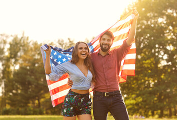 Happy couple with america flag celebrating independence day at sunset.