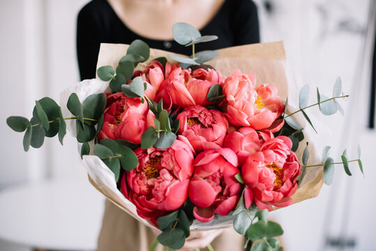 Very nice young woman holding beautiful tender blossoming mono bouquet of fresh coral peony flowers and eucalyptus on the rustic wooden wall background