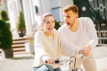 Enthusiastic woman on a bicycle and a man supporting her