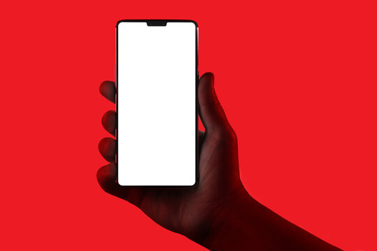 Hand holding phone. Silhouette of male hand holding smartphone isolated on red background. Bezel-less screen is cut with clipping path.