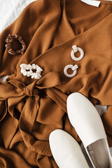 Fashion collage with women's clothes and accessories. Brown dress, white leather slippers,...