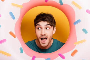 surprised man with open mouth standing with inflatable donut on yellow