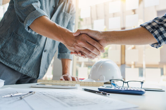 Architect and engineer construction workers shaking hands after success collaboration