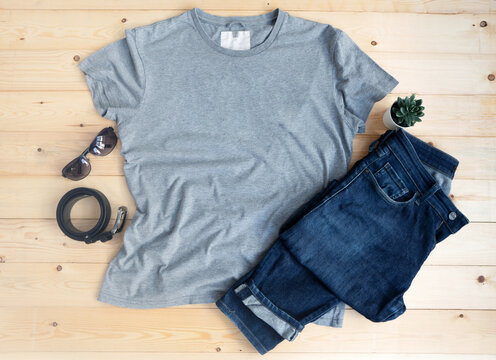 Gray male t shirt mock up flat lay on wooden background. Top front view