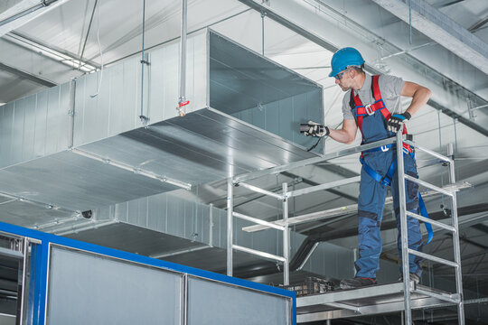 HVAC Technician Testing Newly Installed Warehouse Ventilation System