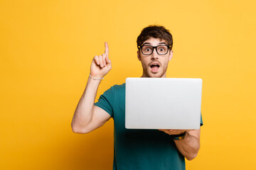 excited young man showing idea gesture while holding laptop on yellow
