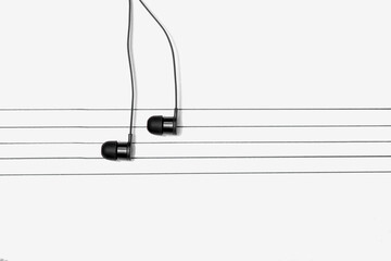 World music day concept. A pair of earphones placed on a staff drawn on a notepad simulating musical notes.