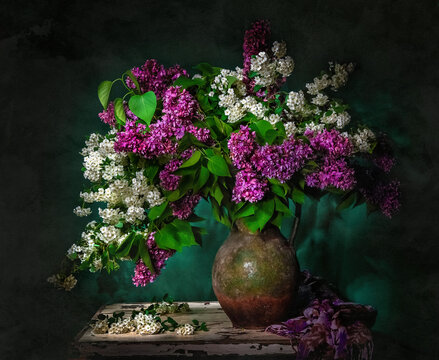 Classic still life with bouquet of beautiful white and purple lilacss in old vintage jug in a ray of light on green background . Art photography.