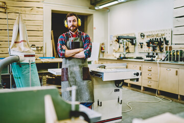 Half length portrait of self-employed woodman in work apron standing in own manufacturing fabric with crossed hands and looking at camera,bearded joiner in protective haedphones for noise cancellation