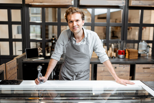 Portrait of a cheerful salesman in apron standing behind the counter of a small shop or cafe. Concept of a small business and work in the field of services