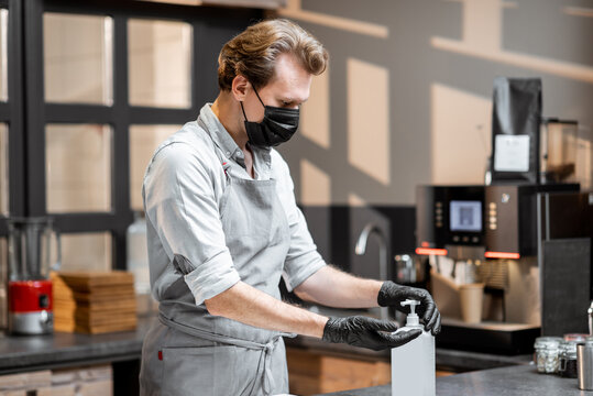 Salesman in protective gloves and face mask disinfecting hands while working in a cafe or small shop. Concept of new social rules for business during a pandemic