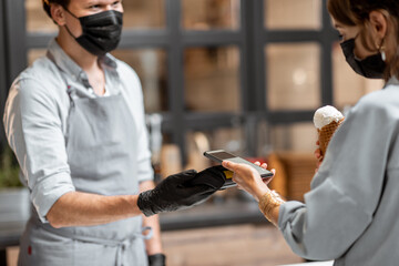 Seller in protective mask and gloves makes contactless payment for a client in the ice cream shop....