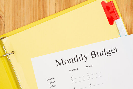 Monthly Budget type message with file tabs in a yellow binder